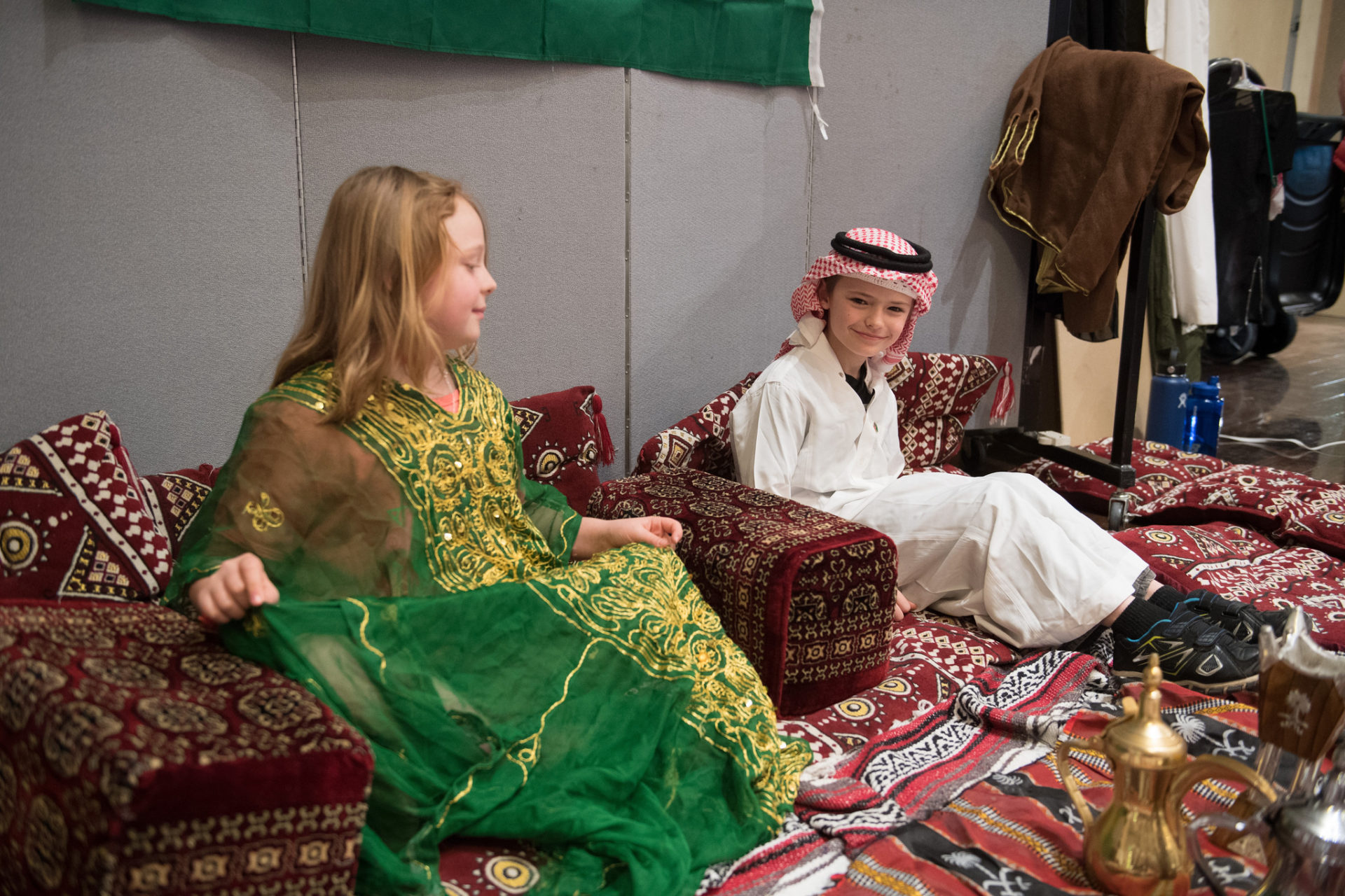 two kids dressed up and sitting on carpets
