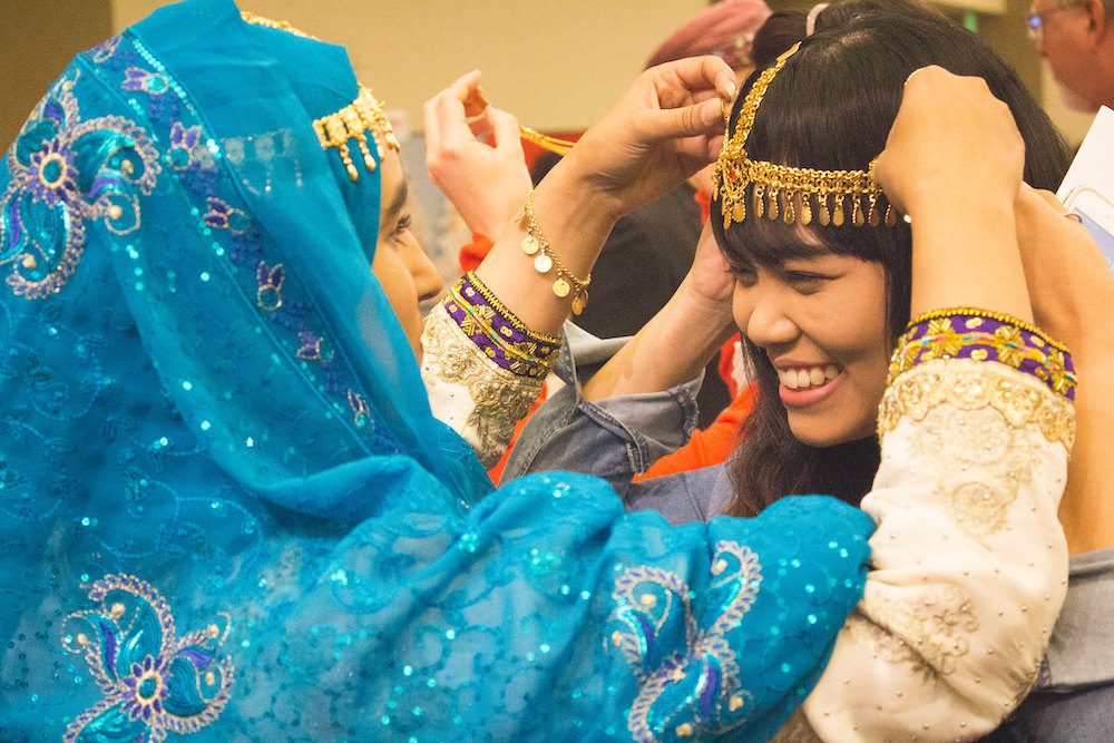 two women putting on traditional accessories from another country