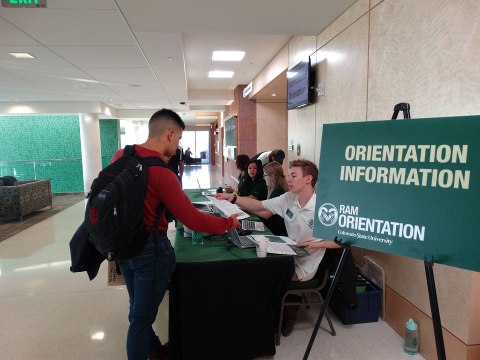 student checking in at an orientation table