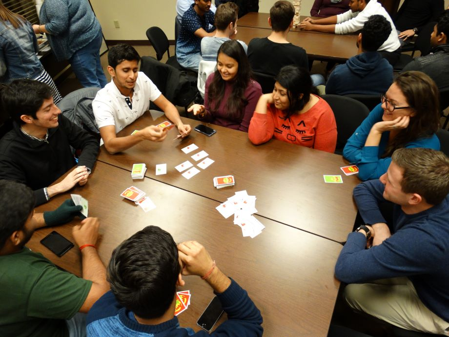 students playing a card game around a table