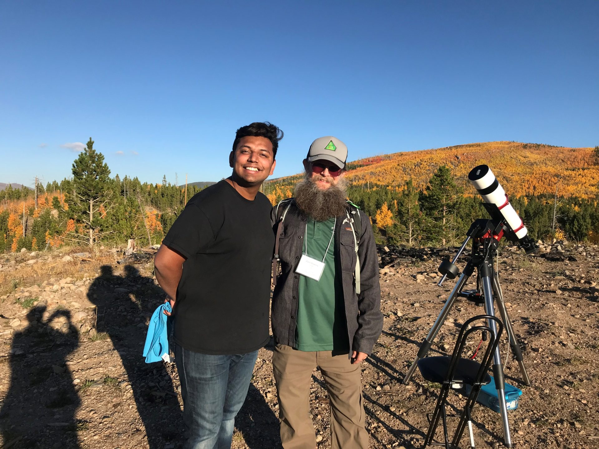 two men with telescope in front of fall folliage
