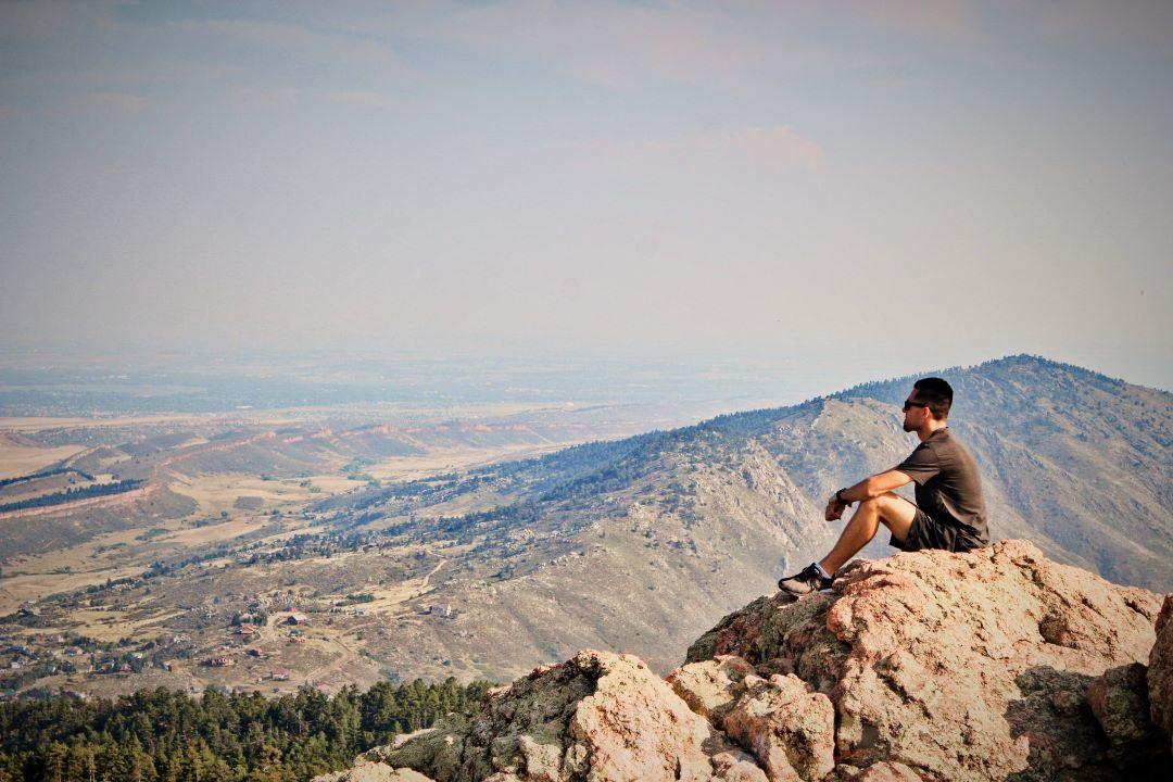 man overlooking hills