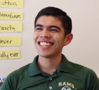 Latino male student with green Rams shirt in front of whiteboard