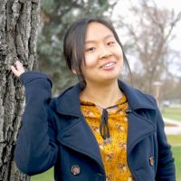 Asian woman waving in front of lawn and trees